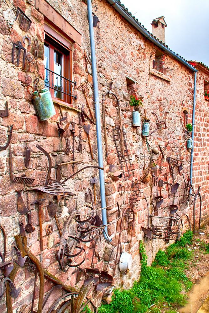 Pared decorada con aperos de hortelano en Prades